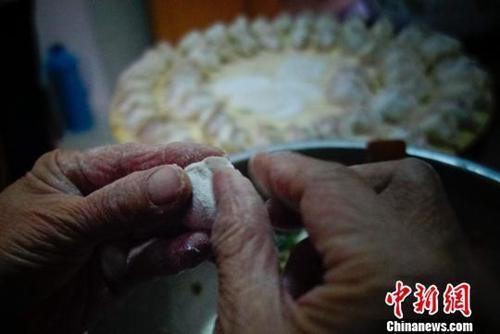 中国侨网资料图:山东省蓬莱市一户家庭为除夕年夜饭包饺子。廖攀 摄