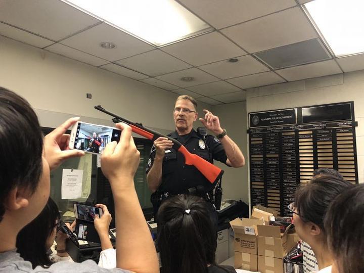 """今年初夏,美国华人聚居城市阿罕布拉举办了一届特殊的""""公民警校""""。阿罕布拉市位于加利福尼亚州洛杉矶东部,是一座约10万人的小城。5月16日至6月20日,阿罕布拉市警察局首次举办面向华人的""""公民警校""""。图为一位警察展示警用枪械。来源:中新社"""